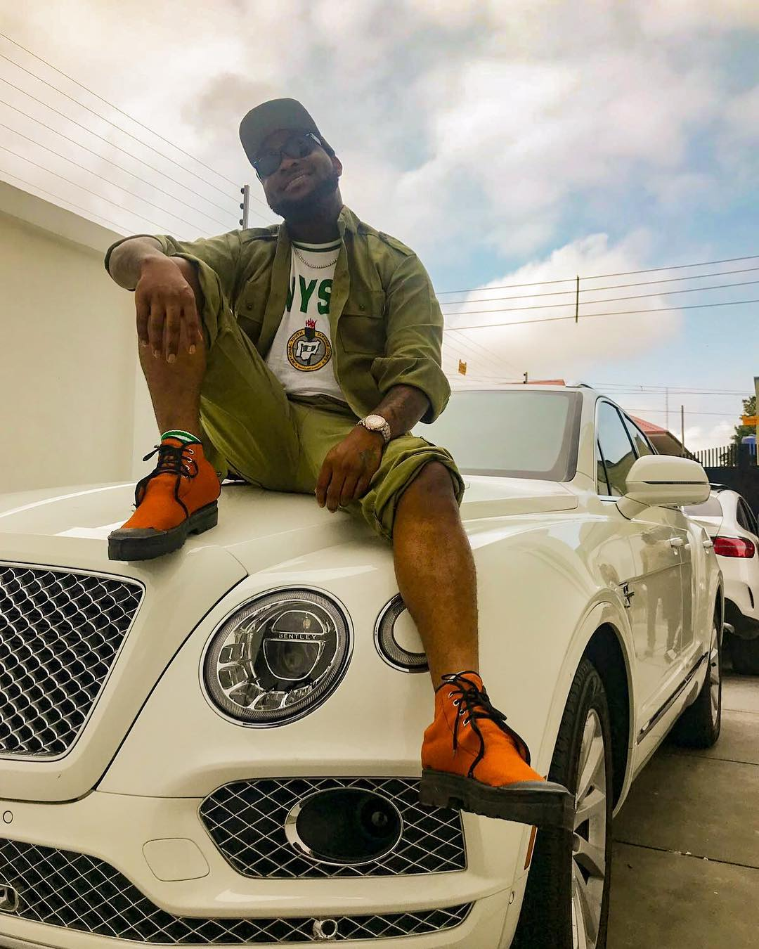 Davido Wearing NYSC Uniform And Sitting On Bentley
